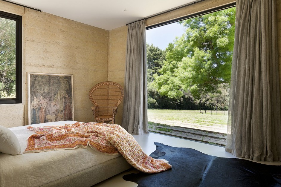 Bed and Flowery Quilt facing the Wide Glass Walls and Outside View