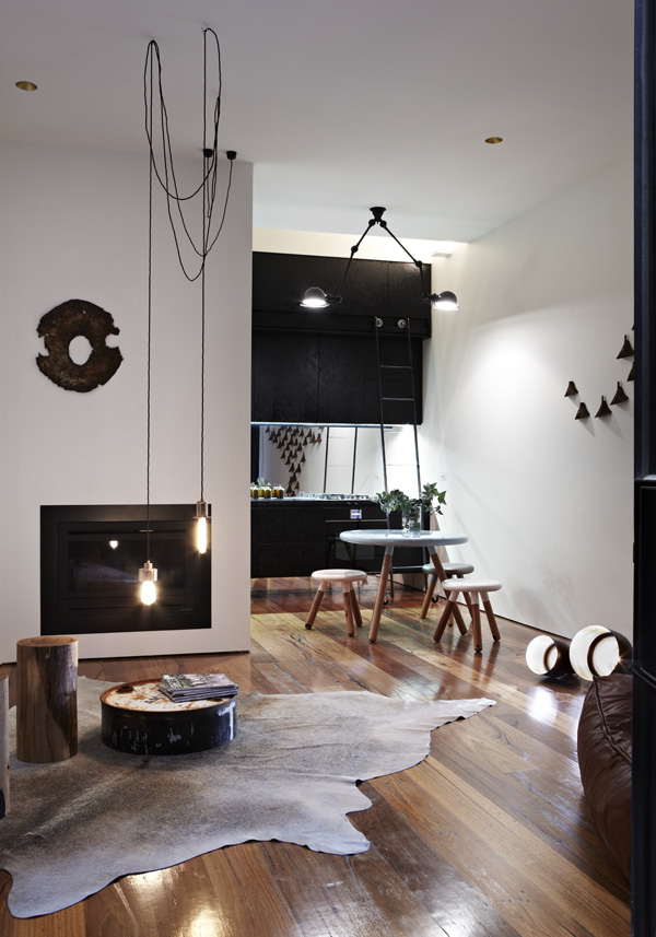 Black Fireplace and White Wall near the Black Kitchen