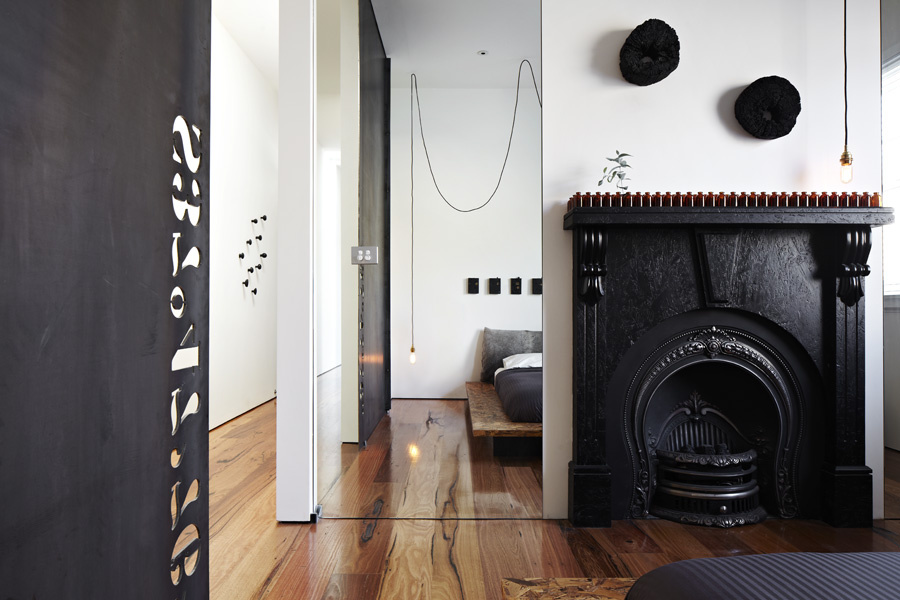 Black Fireplace and Wide Wooden Bed on Hardwood Floor