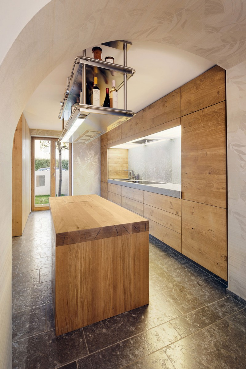 Kitchen Furnished with Built in Wall Cabinetry and Island and Hanging Rack