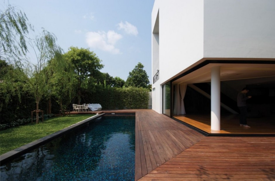 Pool Area Displayed in Courtyard Area with Green Turfs and Deck for Lounge