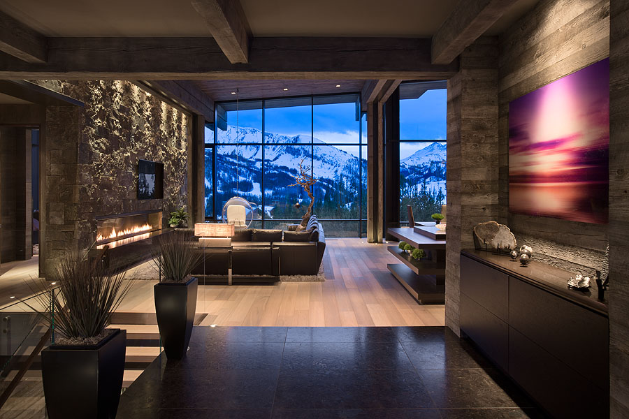 Interior, horizontal, view from foyer toward living area and view out windows of Pioneer Mountain at twilight, Taylor residence, Yellowstone Club, Big Sky, Montana; Reid Smith Architect; LC2 Design Services; Teton Heritage Builders; Montana Reclaimed Lumber