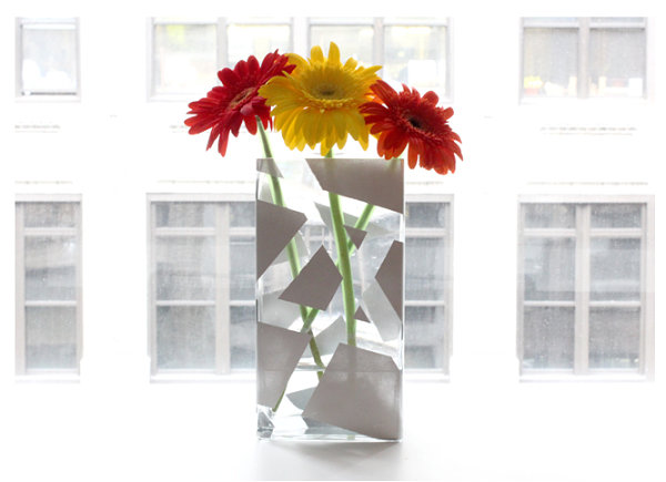 Several Colorful SunfPlaced in Transparent Vase which is Made from Glass Panel with White Ornaments