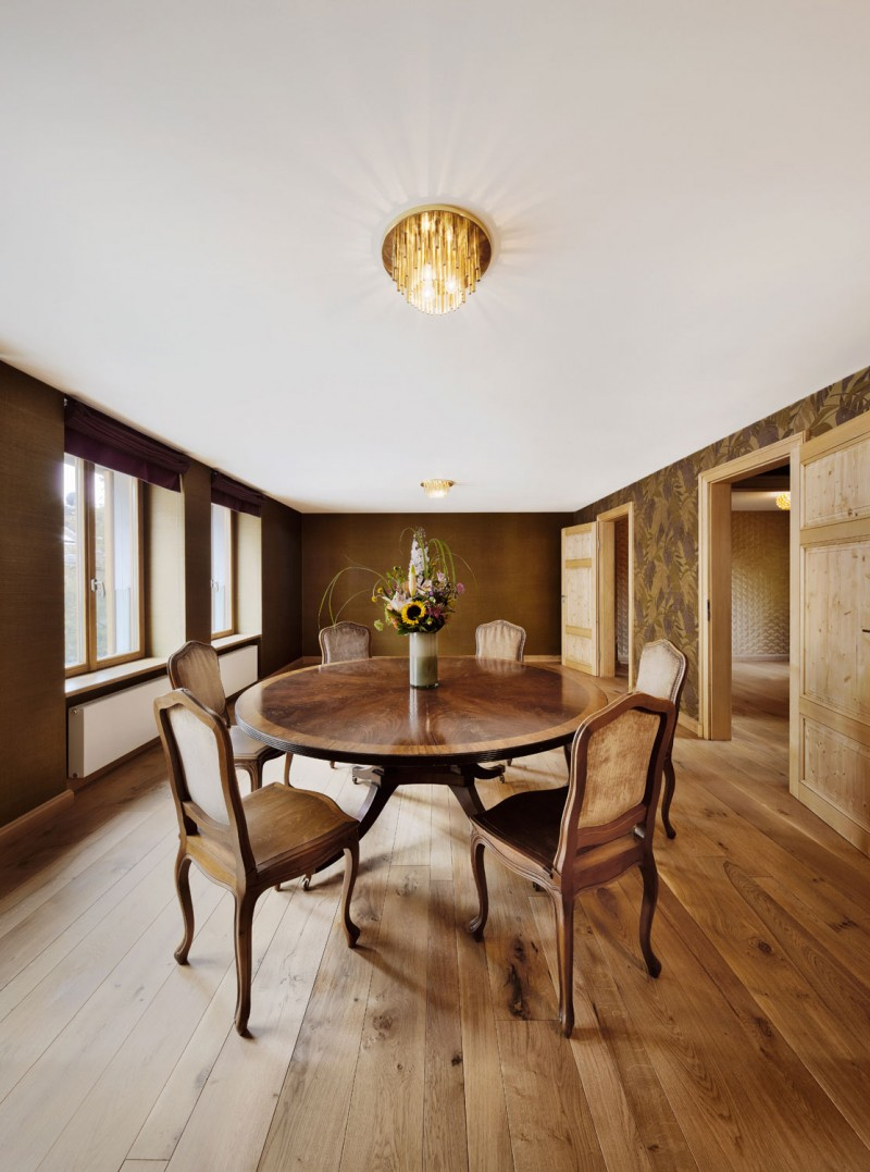 Space with Elegant Wooden Round Table and Chairs Enlightened by Brass Lamp