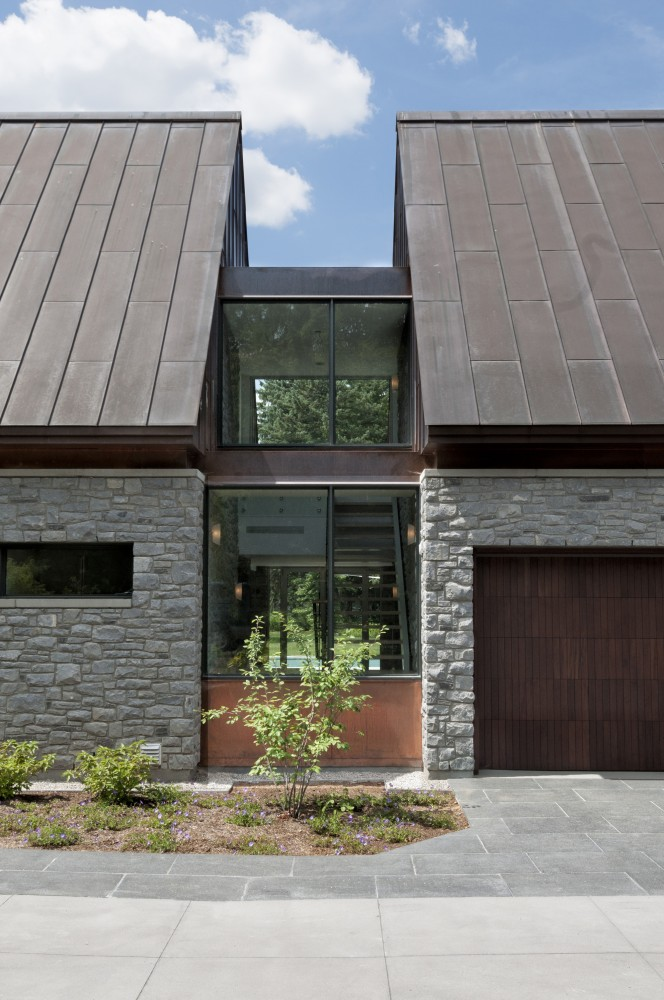Grey Stone Wall and Wide Glass Walls between the Brown Roof