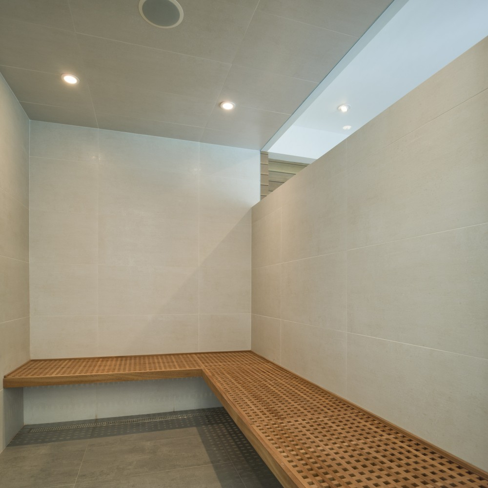 Long Wooden Bench and White Tile Wall above the Grey Floor
