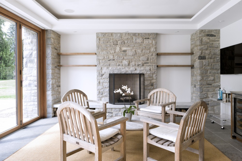 Table in the Living Room with Stone Fireplace and Wide Glass Walls